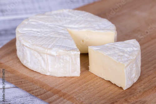 Brie type of cheese. Camembert cheese. Fresh Brie cheese and a slice on a wooden board. Italian, French cheese.