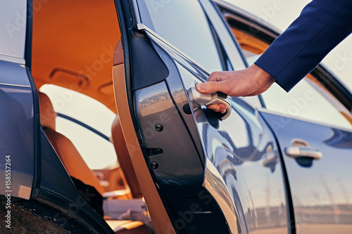 Photographie  Close up image of a man opens car's door.