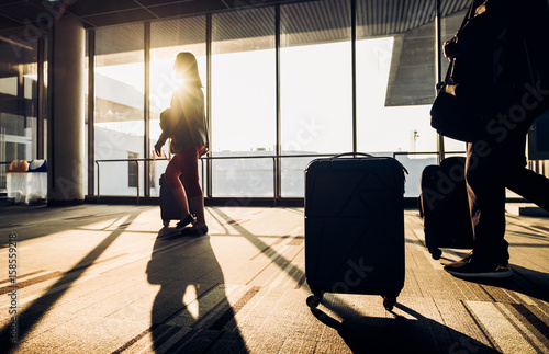 Deurstickers Luchthaven Silhouette of woman walking with luggage walking at airport terminal window at sunrise time,travel concept,journey lifestyle