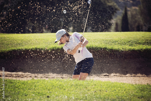 Deurstickers Golf young girl playing golf on a sunny day moving sand in the banker