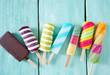 Leinwandbild Motiv colorful popsicle ice cream on turquoise wooden background
