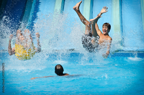 Photo sur Toile Attraction parc Young people having fun on water slides in aqua park, splashing into swimming pool