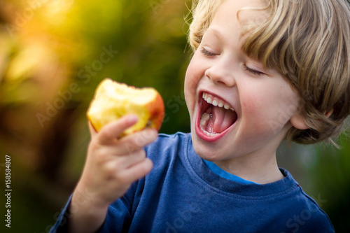 Valokuva  cute blonde child about to take a bite of an apple