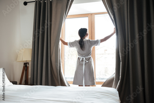Female chambermaid opening window curtains in the hotel room