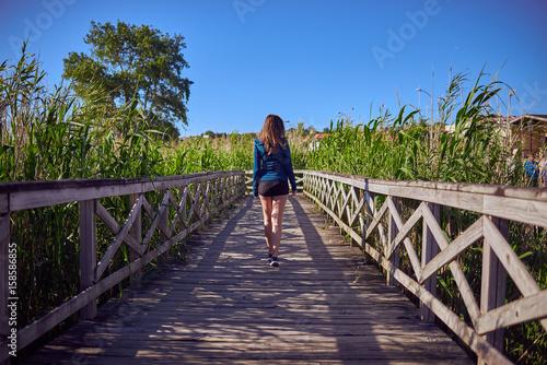 Canvas Print Mujer joven sobre una pasarela de madera