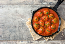 Meatballs With Tomato Sauce In Iron Frying Pan On Wooden Table. Top View