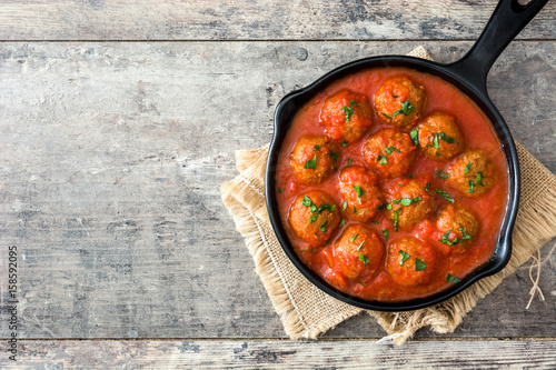 Fotografía  Meatballs with tomato sauce in iron frying pan on wooden table