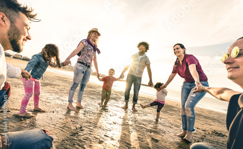 Photo  Happy multiracial families round dancing at the beach on ring around the rosy st