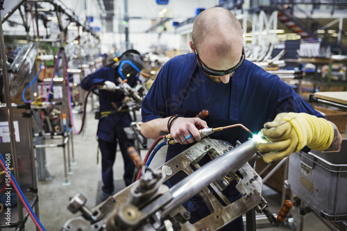 Male skilled factory worker using welding tool, working on bicycle in factory