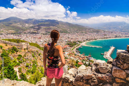 Photo Woman look on landscape of Alanya with marina and Kizil Kule red tower in Antalya district, Turkey, Asia
