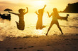 group of girls jumping on the beach - friendship and holidays concept