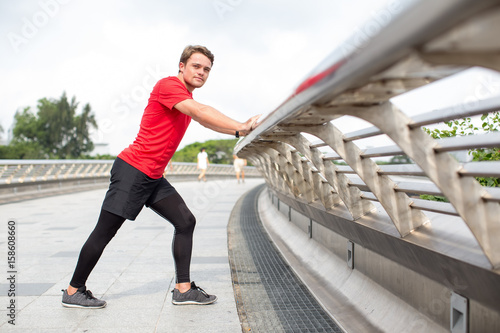 sporty man stretching calf and leaning on railing buy this stock
