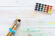 Paint brushes set and box with watercolors on white wooden stained table with splashes, artistic canvas background, tools for creative work, children kids easy painting art, top view with copy space