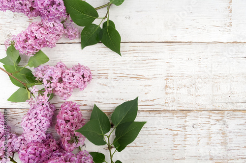 Wall Murals Lily of the valley Spring lilac flowers on white wooden background. Top view, flat lay