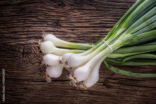Fototapeta Onion. Fresh young onion on rustic oak table. obraz