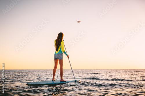 Plakat Atrakcyjna młoda kobieta Stand Up Paddle Surfing i drone copter z pięknymi kolorami słońca