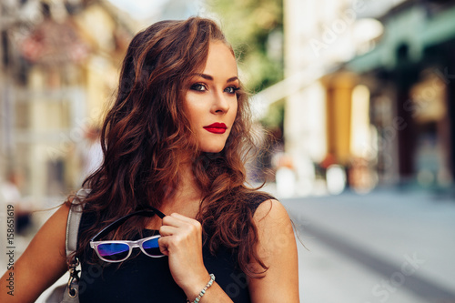 Obraz na plátně Potrait of beautiful young woman with beautiful curly hair and sunglasses in han