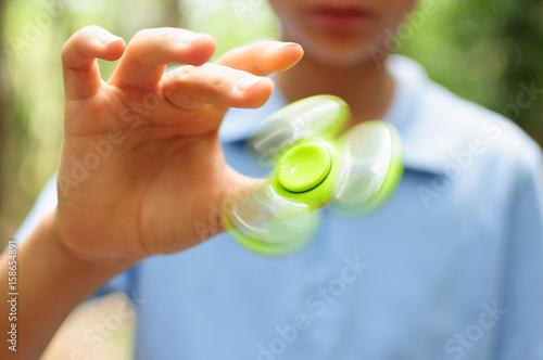 Fotografie, Obraz  Boy playing with a Tri Fidget Hand Spinner