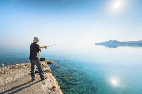 Fotografie, Obraz  Side view of young man fisherman standing on pier with rod