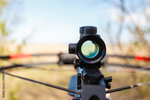 Leinwand Poster Optical sight crossbow aiming from the first person on the background of the lake