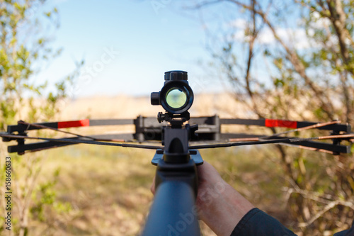 Fotografija A crossbow with a sight to aim in first person on the background of the lake