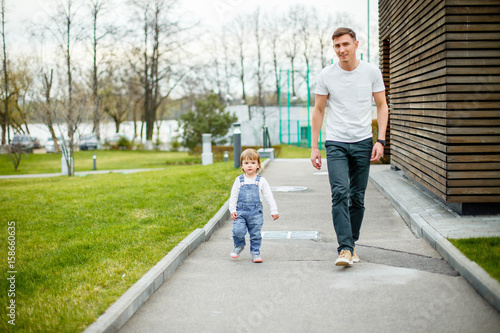 Fotografie, Obraz  A young father with his daughter on a walk in the city park