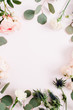 Round frame wreath made of rose flowers, eringium flower, eucalyptus branches on pale pastel pink background. Flat lay, top view. Floral background