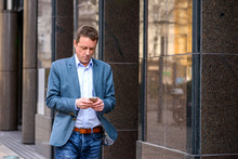 A Middle Age Businessman Walking With A Phone