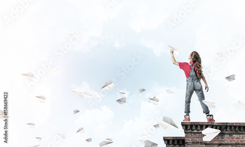 Photo Concept of careless happy childhood with girl dreaming to become