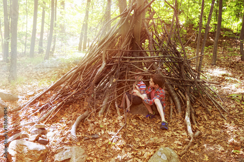 Photo Children play in a hut out of twigs
