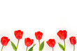 Spring flowers. Composition with red tulip flowers on white background. Flat lay, top view, copy space.