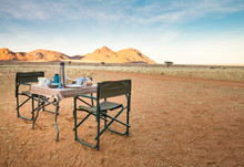 Camping Table And Chairs In The Desert. Great View. Sunrise.