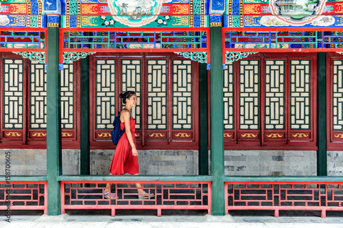 Poster Pekin Young backpacker woman walking through old traditional long corridor at chinese temple, china summer travel. Asian girl visiting tourist attraction in Beijing.