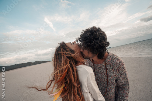 Fotografía beautiful young couple kissing on beach at sunset