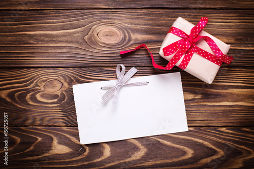 Festive gift box with present on aged wooden background.