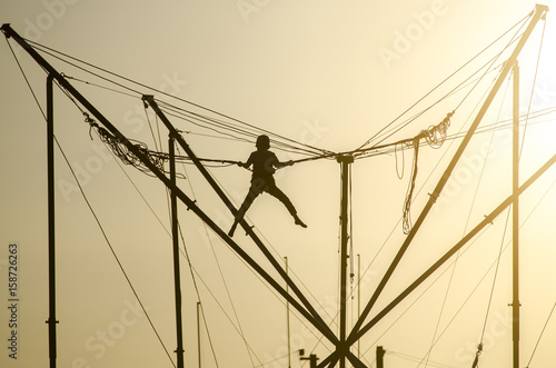 Fotografia Trampoline rope sunset child silhouette