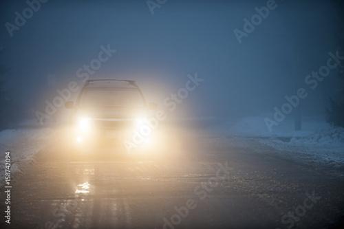 Obraz Headlights of car driving in fog - fototapety do salonu