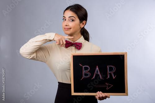 Photo bella cameriera tiene dolcemente una lavagna con scritta BAR e indica la direzio