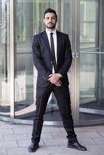 Man Standing In A Suit And Tie In Front Of Glass Door