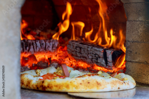 Gourmet Pizza coming out wood fired Pizza Oven in restaurant