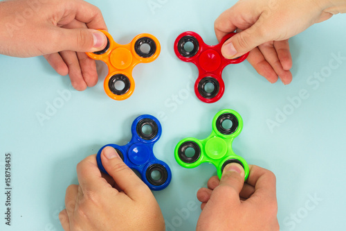 Fotografie, Obraz  trendy fidget spinners - styled flat lay scene with hands holding colorful gener