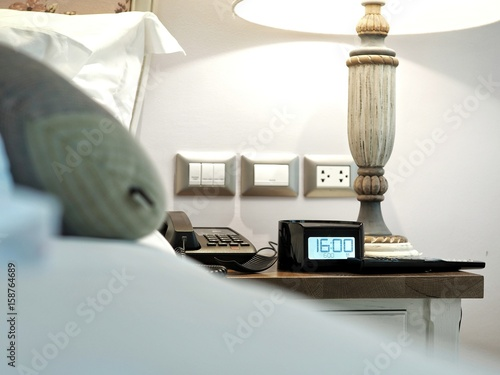 Photo  Hotel room alarm clock on beside table