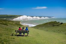 Three People Sitting On A Benc...