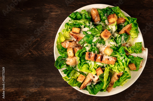 Fotografía Chicken Caesar salad on rustic background with copyspace