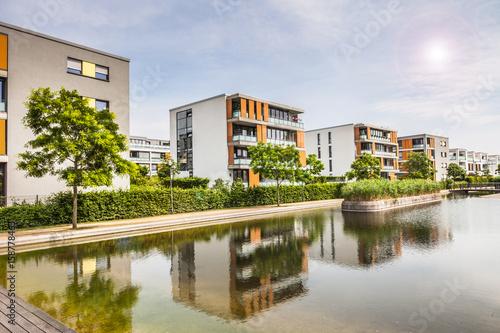 Fotografiet  Neubausiedlung Panorama am Wasser mit Gegenlicht