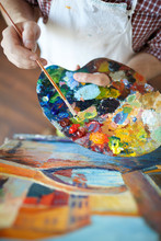 High Angle Shot Of Talented Artist Mixing Colors On Palette While Painting Picture In Art Studio