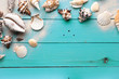 Marine summer postcard. Seashells on turquoise wooden boards in the sand on the beach
