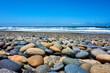 runde Steine im Vordergrund, das Meer und die Wellen im Hintergrund