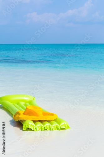 Fototapeta  Green airbed ans hat on beach