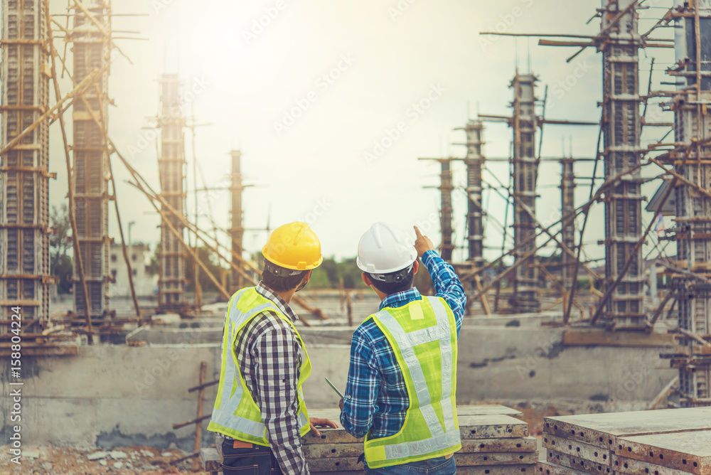 Fototapeta Two young man architect on a building construction site